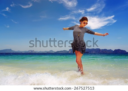 Beautiful girl enjoying the nature in the tropical sea waves - stock photo