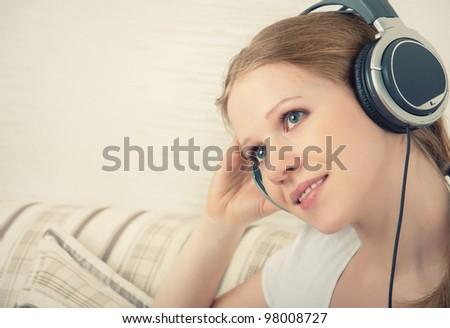 beautiful girl enjoys listening to music on headphones while lying on the sofa - stock photo