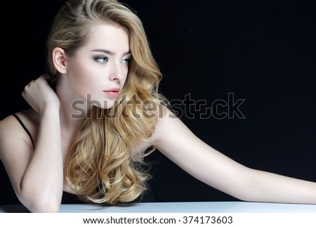 Beautiful Girl face. Perfect skin. Close-up of an attractive girl of European appearance on dark background. - stock photo