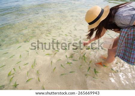 Beautiful girl feeds the fish in Andaman Sea  Krabi Thailand - stock photo