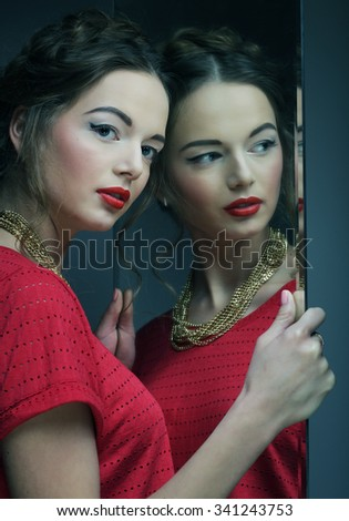 beautiful  girl female model with bright makeup  and her reflection in mirror table  - stock photo