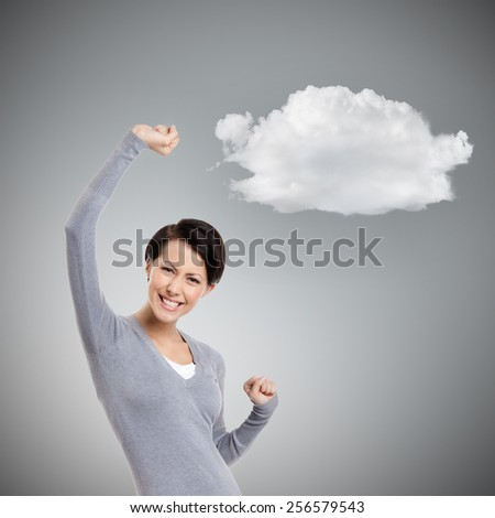 Beautiful girl gestures triumphal fists, isolated on grey background with cloud - stock photo