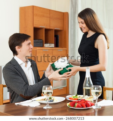 Beautiful girl giving present box to man at table during romantic dinner - stock photo