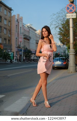 beautiful girl goes across the road in the city - stock photo
