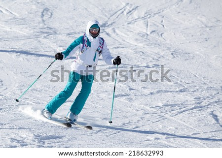 Beautiful girl goes for a drive on skiing - stock photo