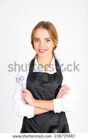 Beautiful girl hairdresser on light background - stock photo