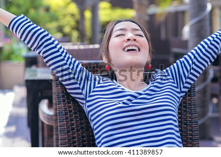 Beautiful girl Hands up in Relaxing time in Outside the coffee shop - stock photo