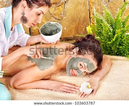 Beautiful girl having clay body mask apply by beautician. - stock photo