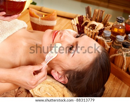 Beautiful girl having clay facial mask apply by beautician. - stock photo