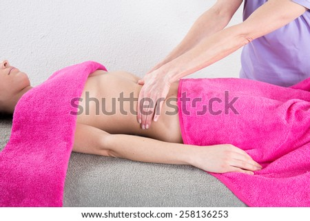 Beautiful girl having stomach massage, ayurveda massage - stock photo
