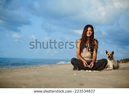 Beautiful girl hippie sitting with his dog on the sea. - stock photo