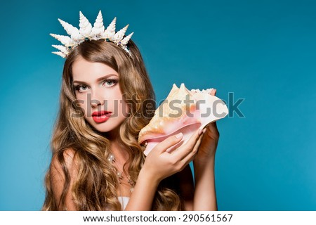 Beautiful girl holding a shell. Mermaid. Sound of the sea in a shell.  - stock photo