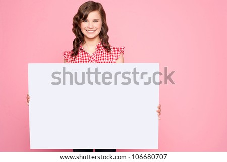 Beautiful girl holding blank billboard and looking at camera - stock photo