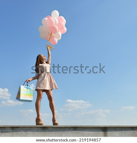 Beautiful girl holding shopping bags and colored ballons over blue sky - stock photo