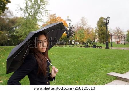 Beautiful girl holding umbrella, thinking of something - stock photo