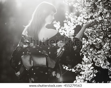 beautiful girl I Japanese clothes in the glow of Solna pulls hands to the cherry blossom, she dressed up as a geisha, black and white image - stock photo