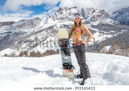 Beautiful girl in a bikini standing with a snowboard on the top of the mountains in Alps - stock photo