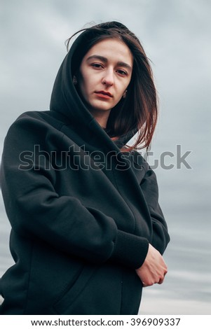 Beautiful girl in a black cloak against the gray sky. Looking in the camera - stock photo
