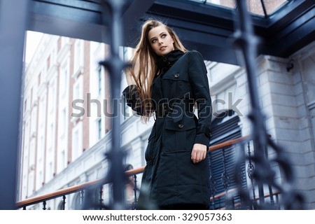 beautiful girl in a black coat walking in the city - stock photo