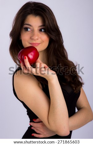 beautiful girl in a black dress holding a red apple - stock photo