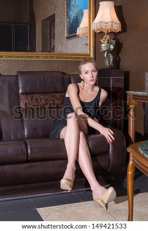 Beautiful girl in a black dress sitting on a leather sofa - stock photo