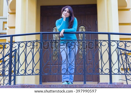 Beautiful girl in a blue turtleneck near the railing. People - stock photo