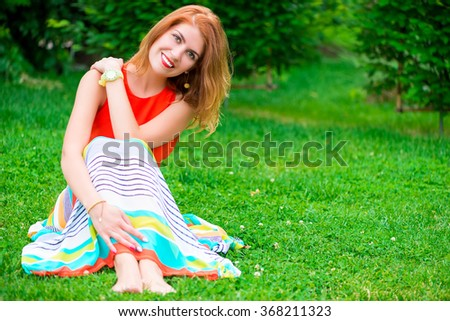 beautiful girl in a bright dress sitting on the grass in the park - stock photo
