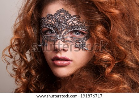 Beautiful Girl in a Carnival mask. Masquerade. Beauty portrait redhead girls.Girl with lush hair.Ginger hair.Woman with voluminous hair - stock photo
