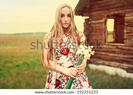 Beautiful girl in a dress standing in a field near the house with flowers on a sunny day - stock photo