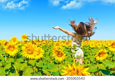 Beautiful girl in a field of sunflowers - stock photo