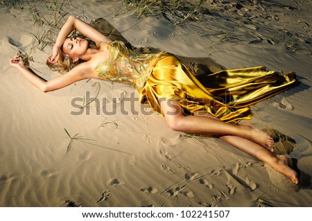beautiful girl in a gold-embroidered corset lying on the sand at sunset - stock photo