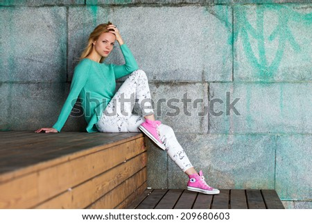 Beautiful girl in a green blouse and pink gumshoes on a concrete wall background - stock photo