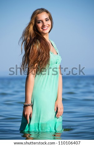 Beautiful girl in a green dress on the coast of the river - stock photo