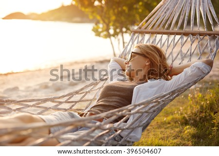 beautiful girl in a hammock on the beach, watching the sunset - stock photo