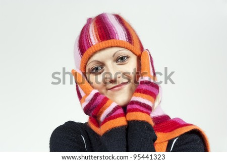 beautiful girl in a hat and gloves, holding a person in the background - stock photo