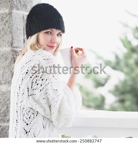 beautiful girl in a hat drinking coffee in the morning in winter - stock photo