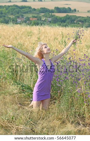 beautiful girl in a lavender dress in a field - stock photo