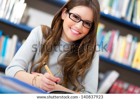 Beautiful girl in a library  - stock photo