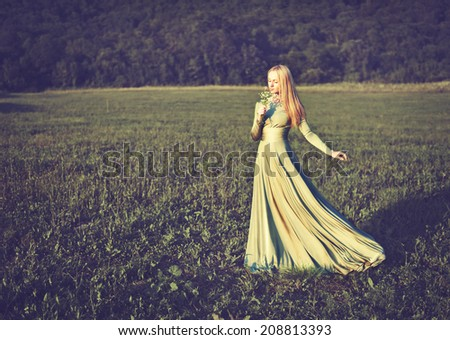 beautiful girl in a long green dress with a bouquet of flowers in the summer on the nature - stock photo