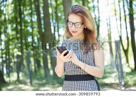 beautiful girl in a park is holding a phone - stock photo