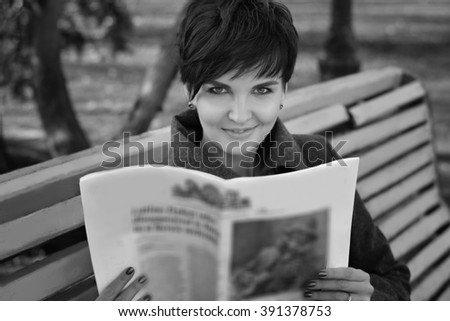 Beautiful girl in a park on a bench reading newspaper and smiling - stock photo