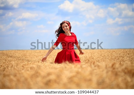 beautiful girl in a red dress walking through a wheat field. - stock photo