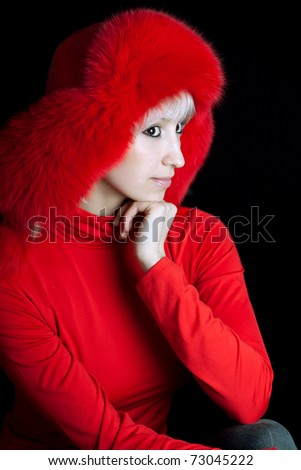 beautiful girl in a red fur hat on a black background - stock photo