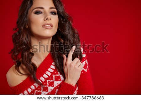 Beautiful girl in a red sweater with white ornaments stands near a red background - stock photo