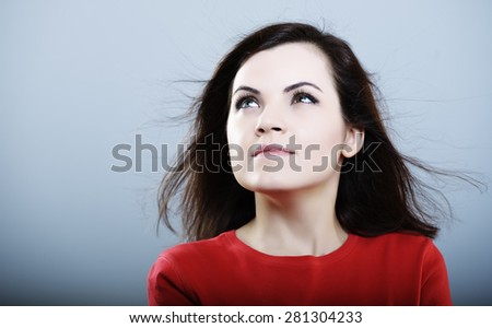 beautiful girl in a red T-shirt with developing hair on a gray background - stock photo