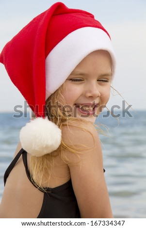 beautiful girl in a santa hat on the beach smiling - stock photo
