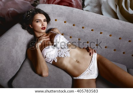 Beautiful girl in a sexy lingerie on a sofa. Fashionable photo of young sexy lady wearing white lingerie, amazing body. Glamour portrait of beautiful woman model with fresh makeup and hairstyle. - stock photo