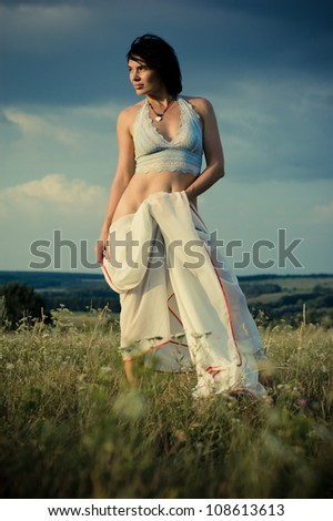 Beautiful girl in a summer field over blue sky - stock photo