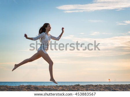 Beautiful girl in a swimsuit on the beach at sunset - stock photo
