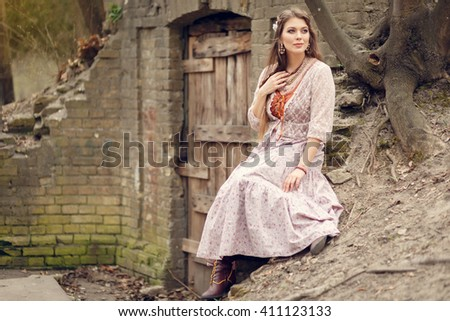 Beautiful girl in a vintage dress sitting and daydreaming in early spring park near old building's door. - stock photo